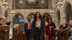 Duas mulheres e um homem andando em uma igreja no primeiro episódio de Pose