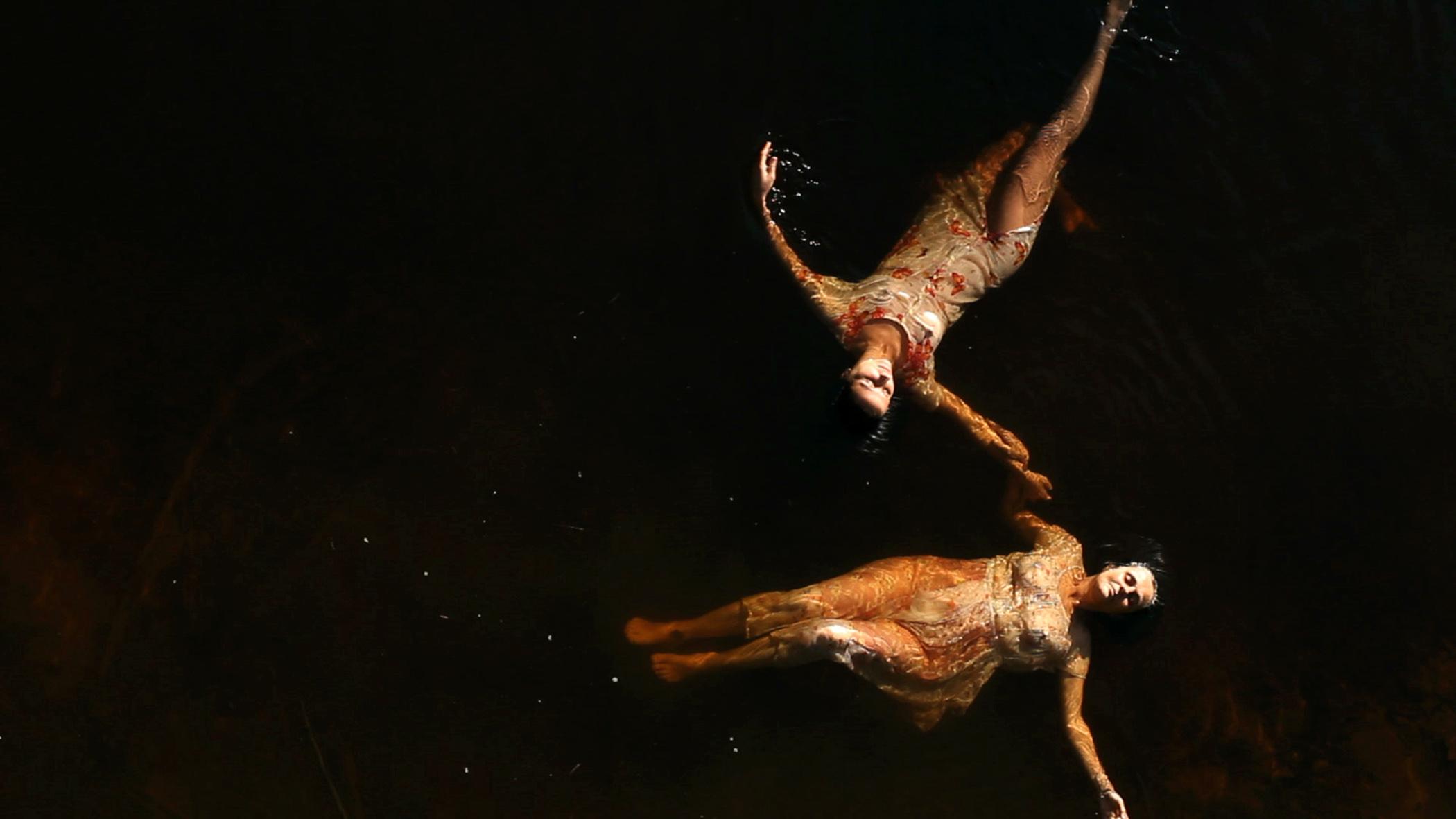 Cena do filme Elena. A imagem mostra duas mulheres flutuando num rio de águas escuras. As duas mulheres estão do lado esquerdo da imagem, e a primeira está na parte de baixo, na horizontal, com a cabeça para o lado direito e os pés em direção ao centro da imagem, virados para o lado esquerdo; e a segunda na parte de cima, de cabeça para baixo, na diagonal. As duas usam vestidos longos em tons de bege. O fundo é preto.