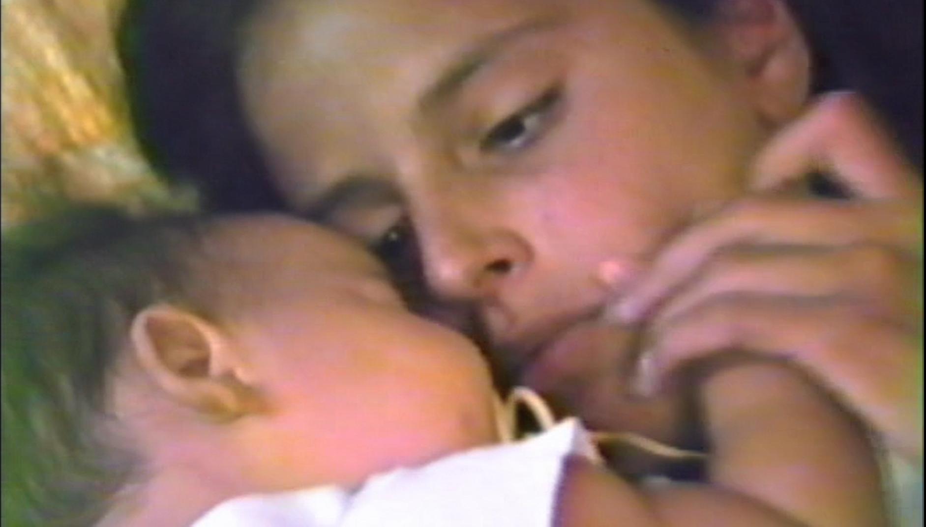 Cena do filme Elena. A imagem mostra Elena e sua irmã Petra ainda bebê deitadas numa cama, num close nos rostos das irmãs. Elena é uma adolescente branca de cabelos lisos, e observa a irmã, no lado esquerdo da imagem, ao mesmo tempo em que segura a sua mãozinha próxima a sua bochecha esquerda. Petra, uma bebê, está deitada, de olhos fechados, abraçada com a irmã, e usa uma chupeta na boca.