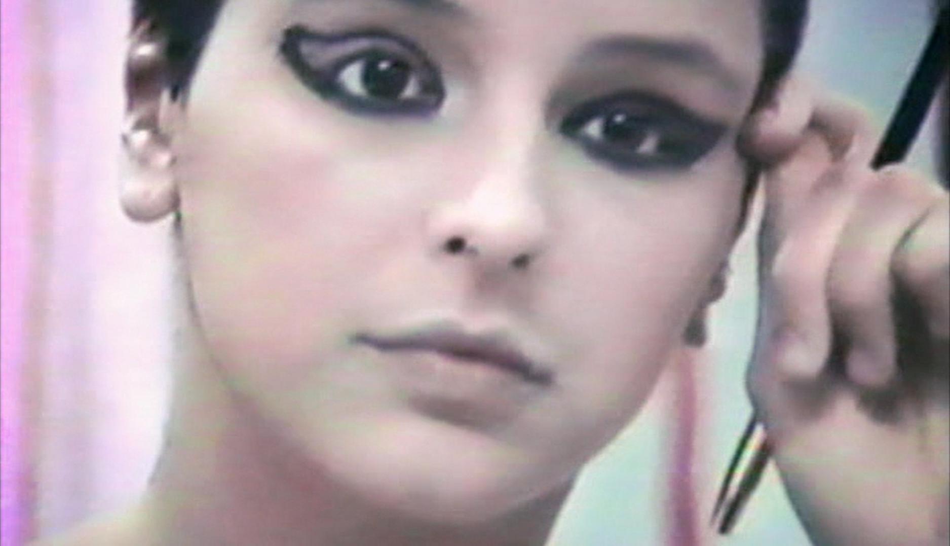 Cena do filme Elena. A imagem mostra Elena adolescente através de um espelho, quando ela se aprontava para uma apresentação de teatro. A imagem é um close em seu rosto, e ela é uma jovem branca, com os cabelos presos, e está fazendo uma maquiagem preta nos olhos.