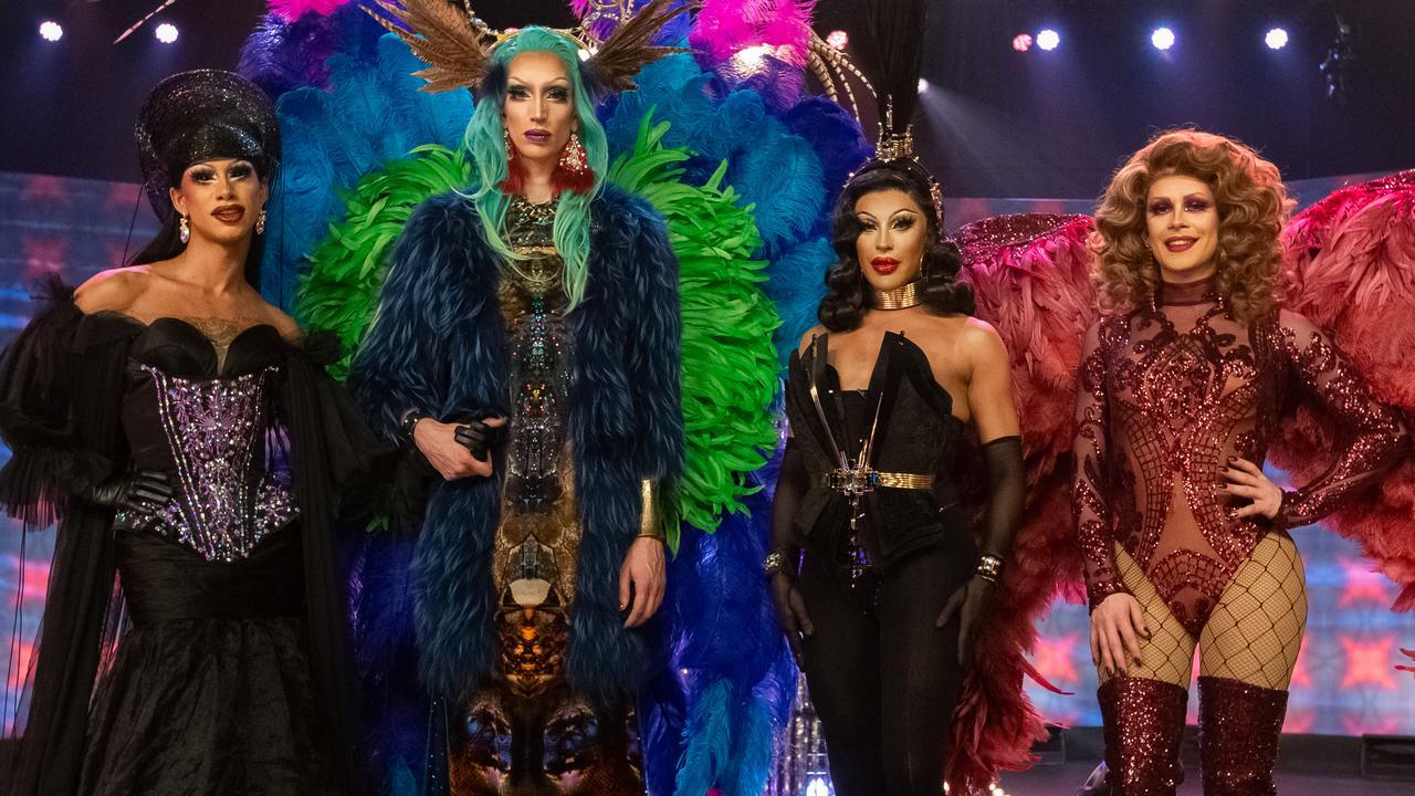 Na foto vemos quatro drag queens. Da esquerda para a direita: Miss Abby OMG está toda de preto, com um espartilho roxo, Ma'ma Queen usa uma roupa azul e verde, com plumas e asas que lembram o carnaval, seu cabelo é azul claro e ela tem um adereço na cabeça, Envy Peru está de preto com uma grande pluma na cabeça e Janey Jacké veste vermelho, um maiô com meia calça e asas de anjo no mesmo tom de vermelho.