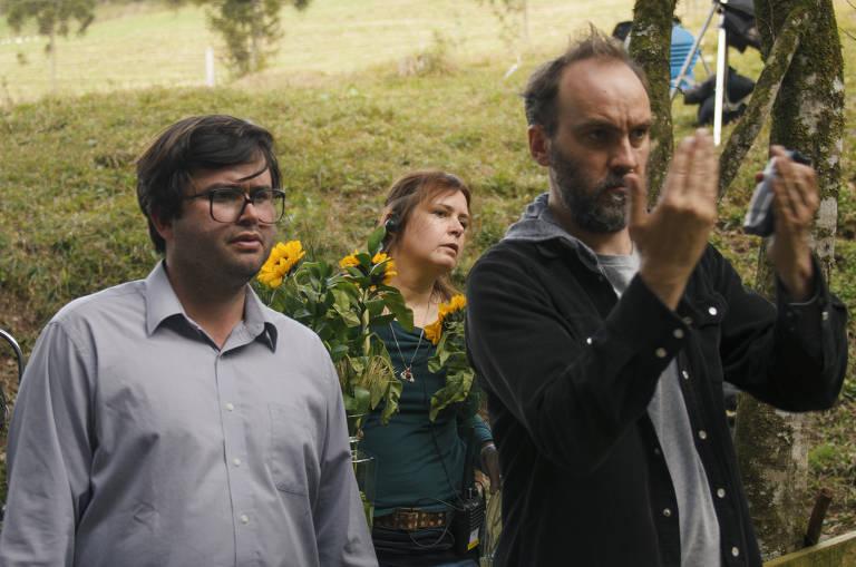 Bastidor do filme, o diretor, um homem branco e de camisa social e óculos, está ao lado de um homem mais alto que ele, de barba e calvo, que dá alguma indicação manual. O fundo da imagem é um campo verde