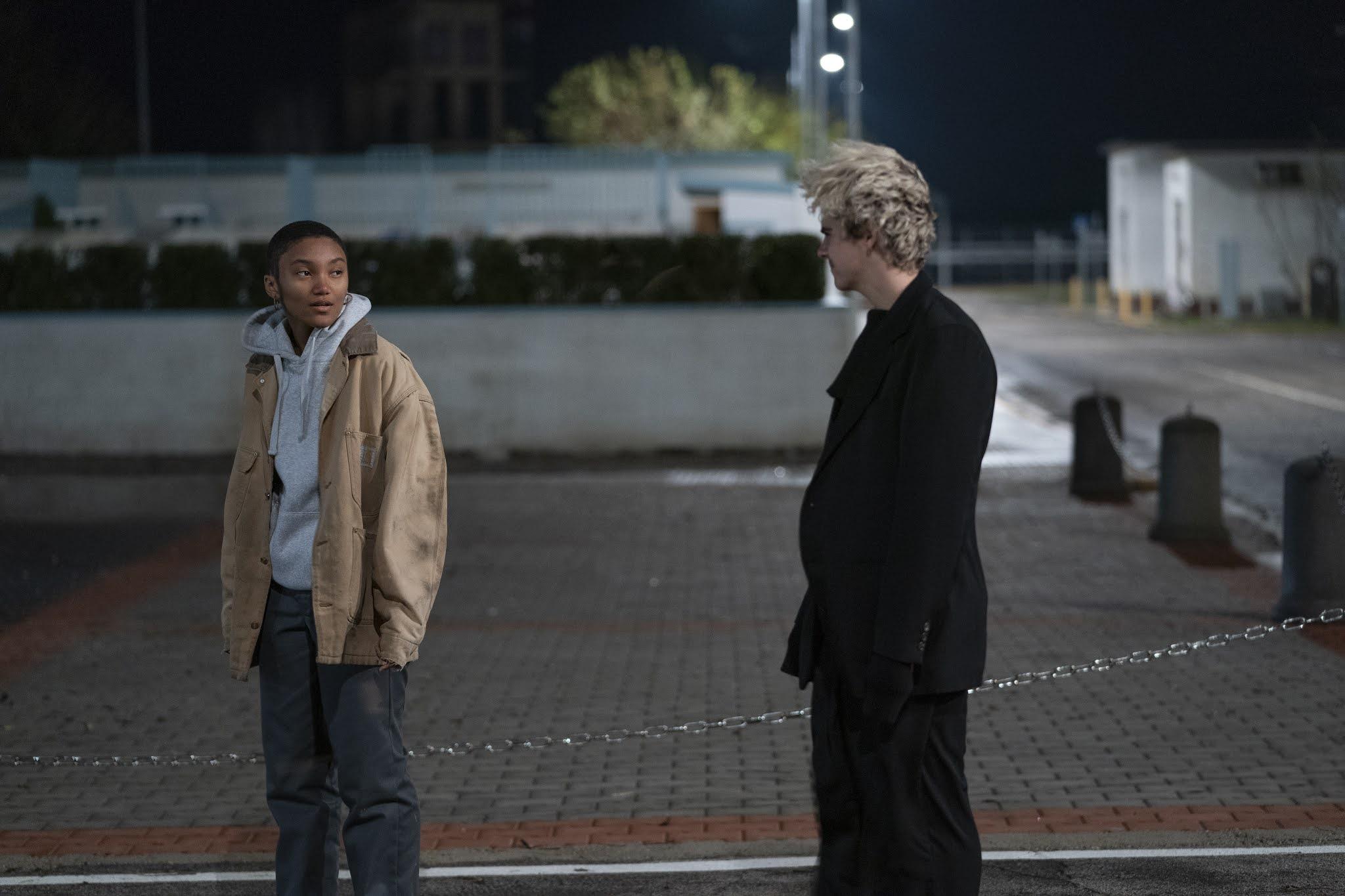 Na foto vemos dois jovens numa rua da Itália. Caitlin é uma menina negra, de 14 anos e cabelos raspados. Ela usa uma calça jeans escura e larga, um moletom cinza e uma jaqueta bege por cima. Fraser é um menino branco de 14 anos, ele tem o cabelo descolorido loiro e usa só roupas pretas. Eles se olham, e estão alguns passos distantes.