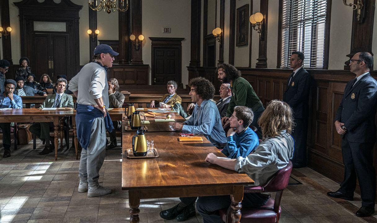 A imagem é uma fotografia dos bastidores da gravação do filme. Na imagem, vemos o cenário do tribunal. Nele, o diretor, Aaron Sorkin, está posicionado em frente à mesa do réu, conversando com os atores, que estão sentados em cadeiras do outro lado da mesa.