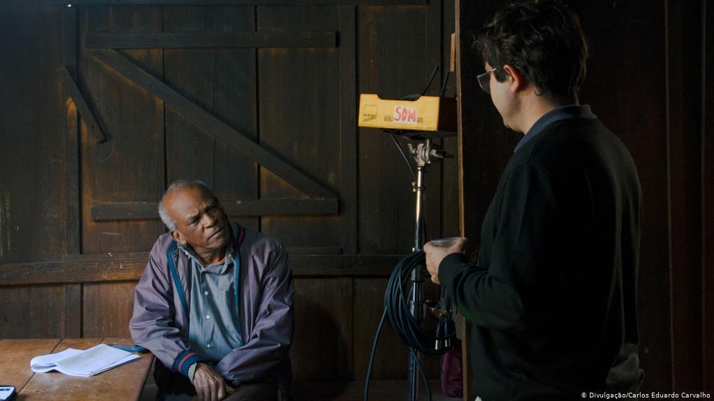 Foto dos bastidores do filme, onde Antonio Pitanga, um homem negro e idoso, está sentado à mesa, olhando para o diretor Miranda Maria, um homem branco que está de costas para a câmera. Ao lado deles, existe um tripé