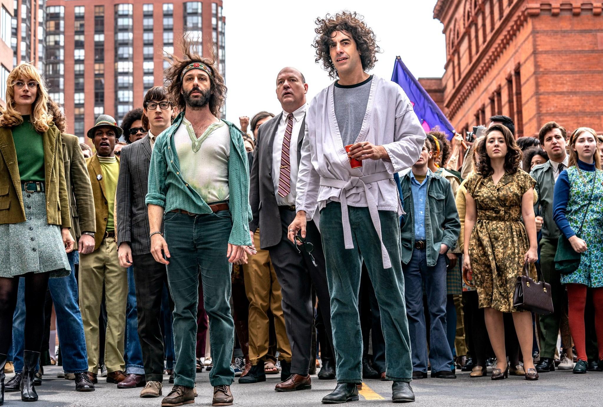 A imagem mostra uma das cenas de protestos do filme. Nela, há uma multidão de ativistas em pé, encarando o horizonte assustados. À frente dessa multidão, vemos, da esquerda para a direita, os personagens Rennie Davis, Jerry Rubin, David Dellinger e Abbie Hoffman.