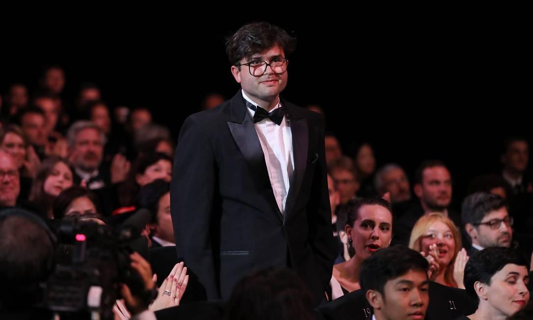 O diretor, um homem branco usando óculos e terno preto, está em pé em meio a uma plateia no Festival de Cannes, ele sorri