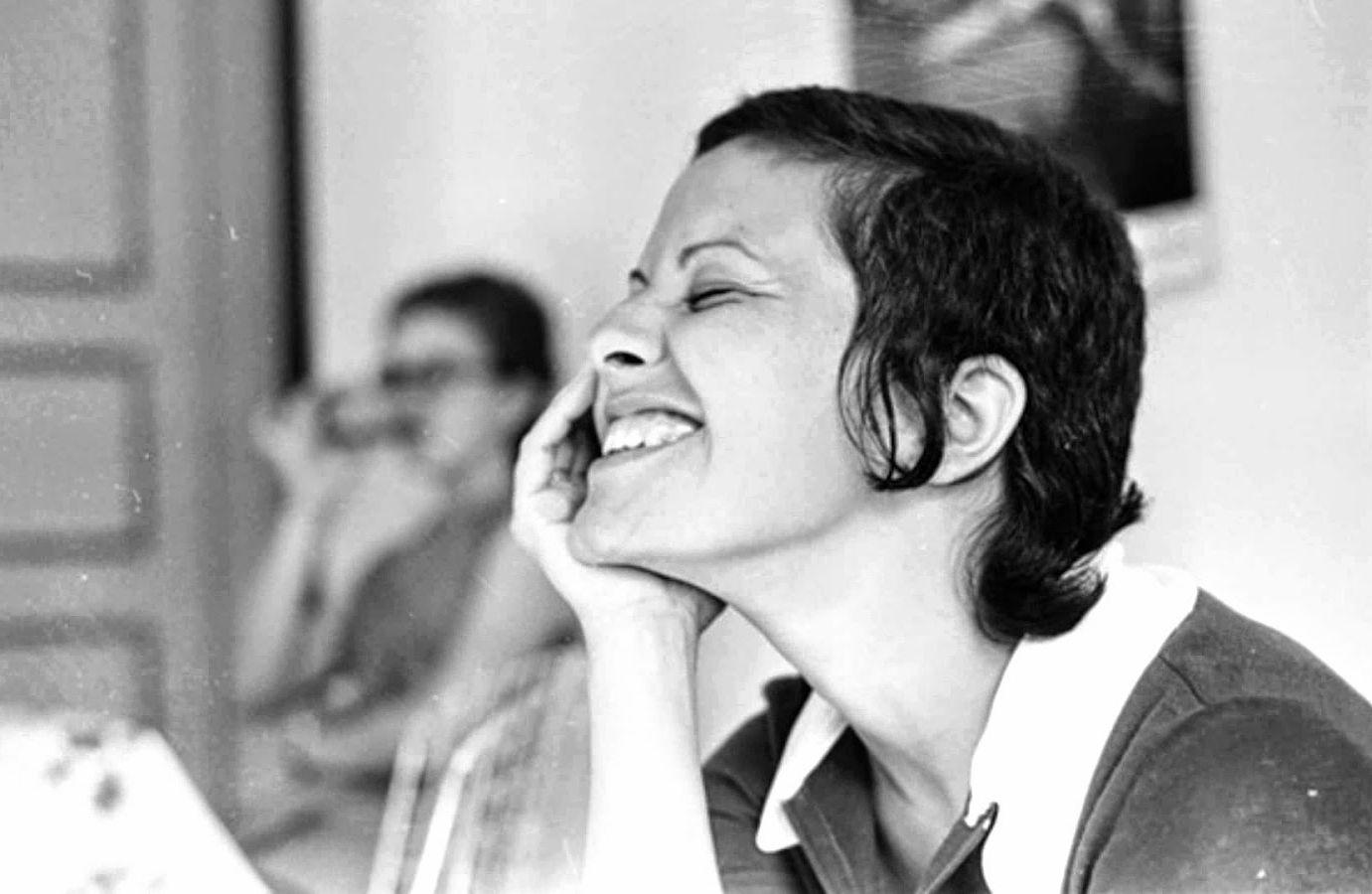 Imagem em branco e preto de Elis Regina sorrindo de perfil. Ela tem a mão direita apoiando o rosto e ao fundo a imagem desfocada de uma pessoa.