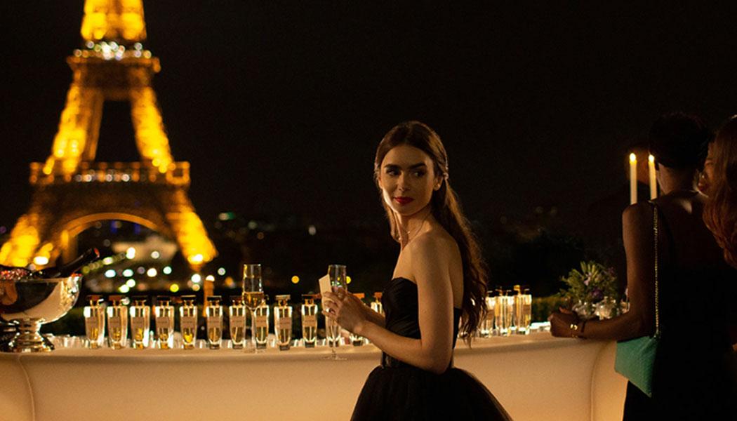 A imagem é uma foto de uma cena da série. Na imagem, a personagem Emily está posicionada com o corpo virado de lado, para a esquerda, e seu rosto virado para a direita. A personagem usa um vestido preto, está com os cabelos longos semi-presos e segura uma taça em suas mãos. Atrás de Emily, há uma mesa com várias bebidas, o que parece ser um bar. Ao fundo da imagem, é possível ver parte da Torre Eiffel iluminada.