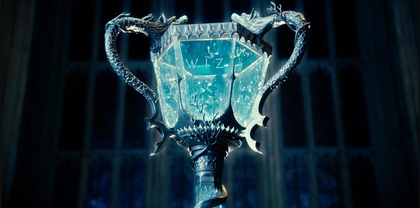 A imagem mostra a taça do torneio tribruxo, a qual é transparente com sua base e alças em um prata decorado. Dentro da taça há um líquido azul. Ao fundo há uma grande janela.