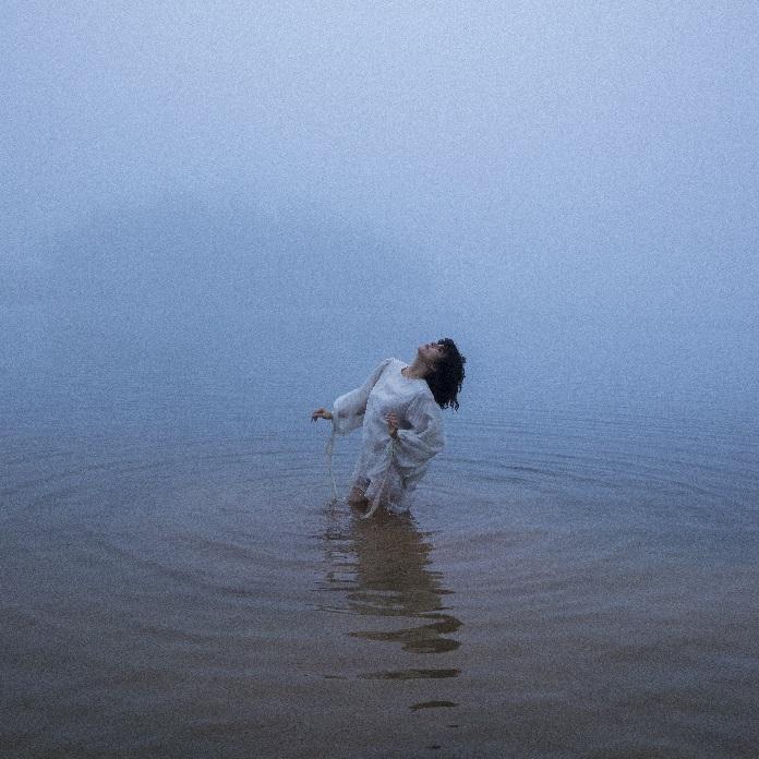 Foto da artista Maria do Céu. Ela está num lago cujo final se mistura com o início do céu, e está imersa na água até os joelhos. Usa um vestido branco com mangas bufantes, e seu corpo é levemente inclinado pra trás para olhar em direção ao céu. Suas mãos estão paradas naturalmente flexionadas na altura da cintura.