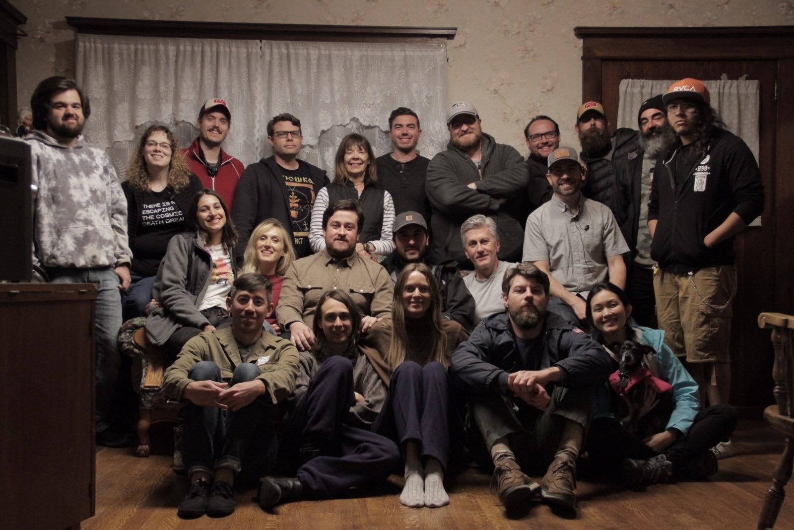Fotografia dos bastidores do filme. Cerca de 25 pessoas posam para a foto, sorrindo, eles estão reunidos, alguns estão sentados no sofá e os demais estão ou sentados no chão na frente do sofá ou de pé atrás do sofá.