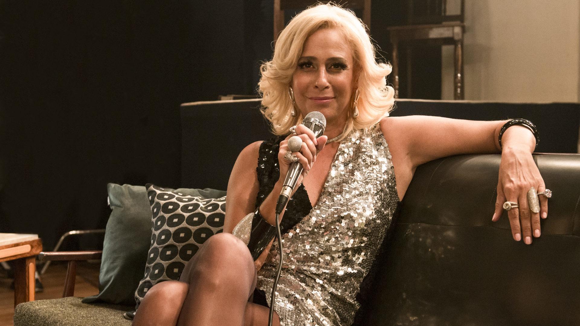 A imagem é uma fotografia de Andréa Beltrão caracterizada como Hebe. A atriz está sentada em um sofá com as pernas cruzadas e o braço esquerdo apoiado no encosto do sofá. A atriz está com cabelo loiro curto, e veste um vestido prateado e preto. Ela também segura um microfone em sua mão direita.