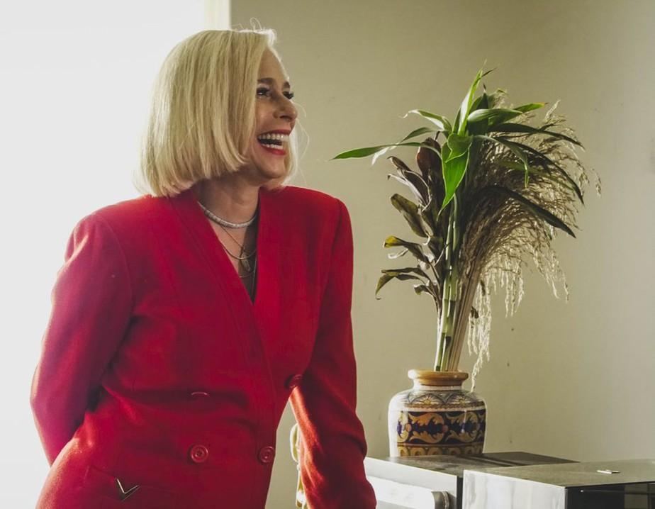 A imagem é de uma cena da minissérie. Nela, Andréa está à esquerda, caracterizada como Hebe. A atriz está com cabelos loiros curtos em corte chanel, ela usa batom vermelho, colares e está com um casaco vermelho. A atriz está virada para o lado, sorrindo. Ao fundo, do lado direito, há um vaso com uma planta.