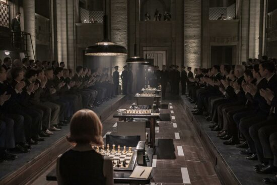 Cenário marrom e escuro de uma partida de xadrez, com Beth senteda de costas com um tabuleiro na frente