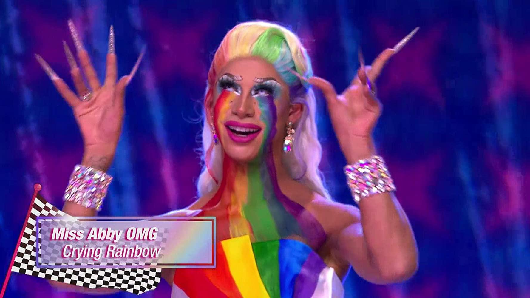 Miss Abby OMG, uma drag queen de pele clara e cabelos loiros sorri com os olhos e as mãos para cima, ela tem as cores do arco-íris pinadas em seu peito, que encontram o tecido do vestido, que mantém o padrão de cores