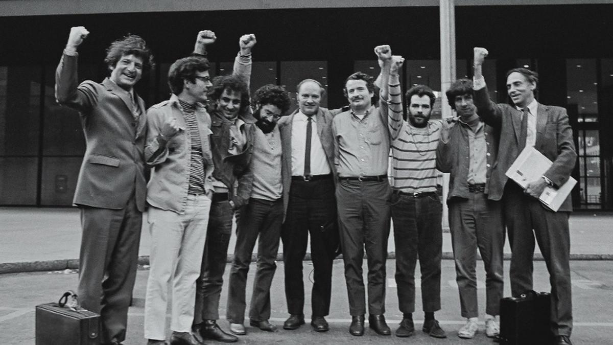 A imagem é uma fotografia dos verdadeiro Sete de Chicago e seus dois advogados. Na imagem, eles estão posicionados em fileira se abraçando, alguns deles estão com os punhos levantados, em sinal de vitória.