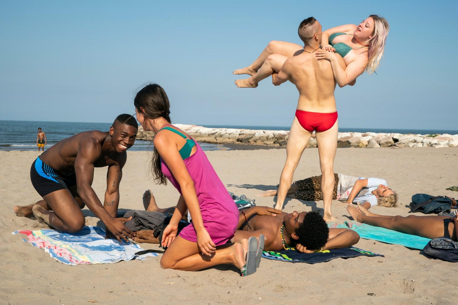 Os adolescentes estão na praia. Deitados na areia estão Craig, jovem negro e de sunga azul, Danny, negro e de shorts azul, Fraser, branco e de calça estampada de oncinha e camiseta branca. Francesca, menina branca e loira, é pegada no colo por um garoto alto, que está usando sunga vermelha.