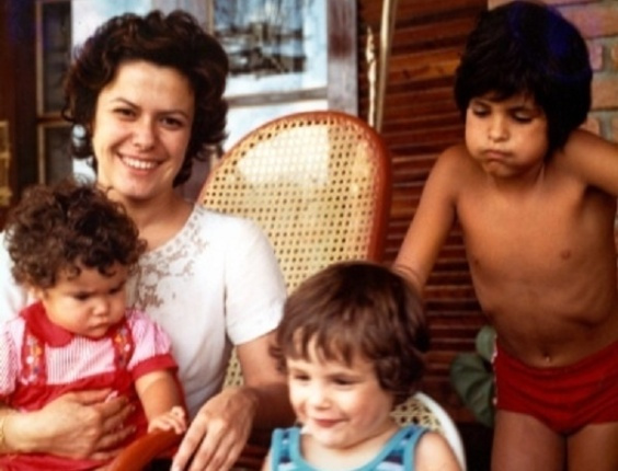 Imagem de Elis regina com seus filhos. Ela está sentada em uma cadeira e segura Maria Rita, ainda pequena, em seu colo. Ao lado dela estão seus dois filhos mais velhos.