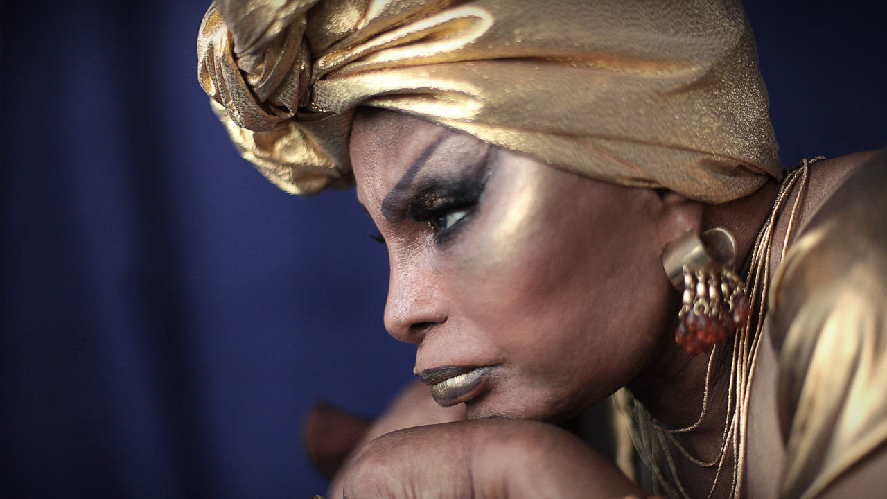 Foto de Elza Soares. A artista está de perfil e muito próxima da câmera, usando um turbante dourado, batom cintilante e um brinco vermelho. Sua expressão é séria e ela olha para a frente.