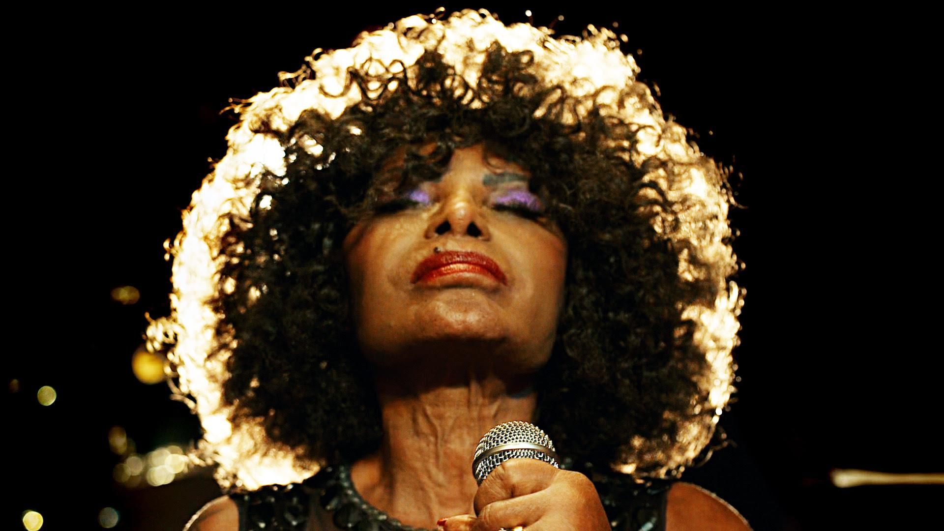 Foto de Elza Soares. A artista está ao centro da imagem, segurando um microfone de olhos fechados e atrás dela existe um fundo preto, usando uma maquiagem roxa nos olhos e batom vermelho.