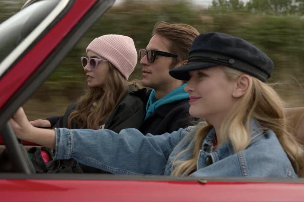A imagem é uma fotografia de uma das cenas da série. Nela, Emily e outros dois personagens estão em um carro vermelho em movimento. No volante, há uma mulher branca, loira com cabelos longos, ela usa uma boina preta e uma jaqueta jeans. Ao seu lado, está um homem branco, com cabelos castanhos claros, ele usa um óculos escuro e um casaco preto. Junto com ele, está Emily. Emily é uma mulher branca, de cabelos castanhos longos. Emily usa um gorro rosa, óculos escuros com armação rosa e veste um casaco preto.