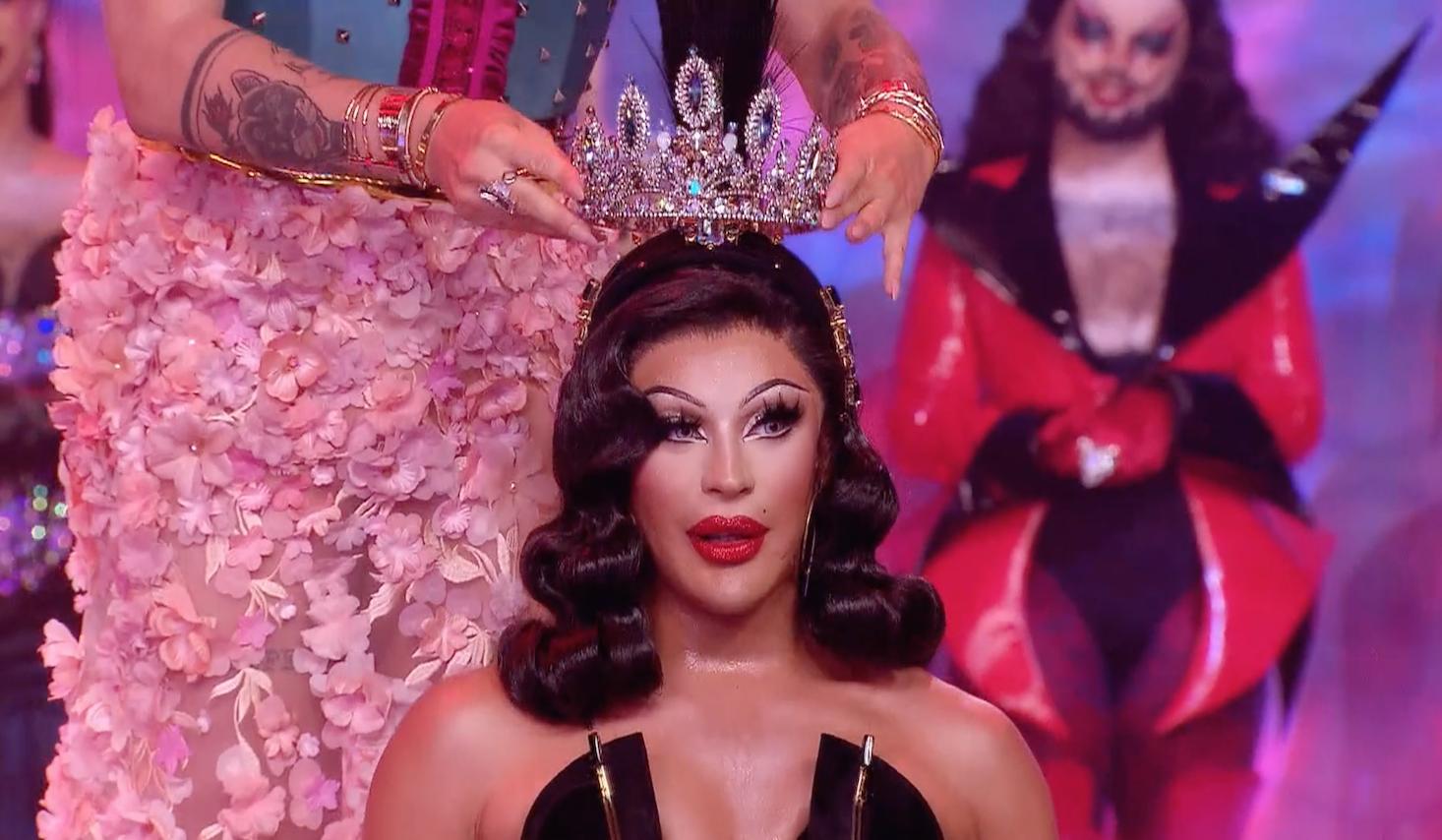 Envy Peru, uma drag queen latina de pele clara recebe a coroa das mãos de uma pessoa fora de enquadramento.