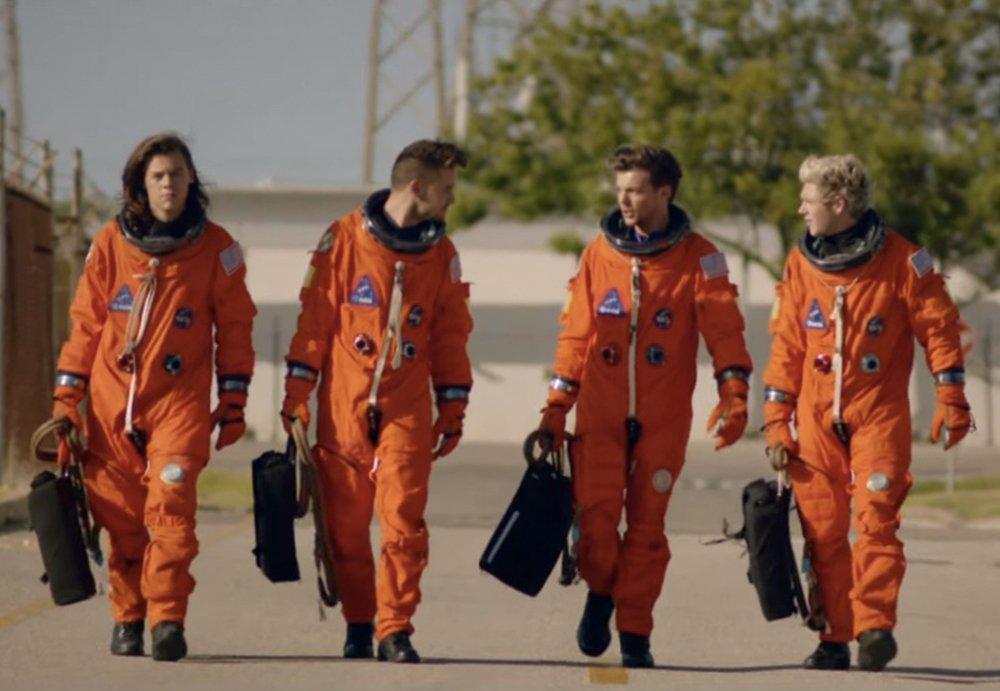 A imagem mostra os quatro integrantes do One Direction, vestindo roupa de astronauta, em cor laranja. Eles não usam capacete e estão andando em direção à câmera.