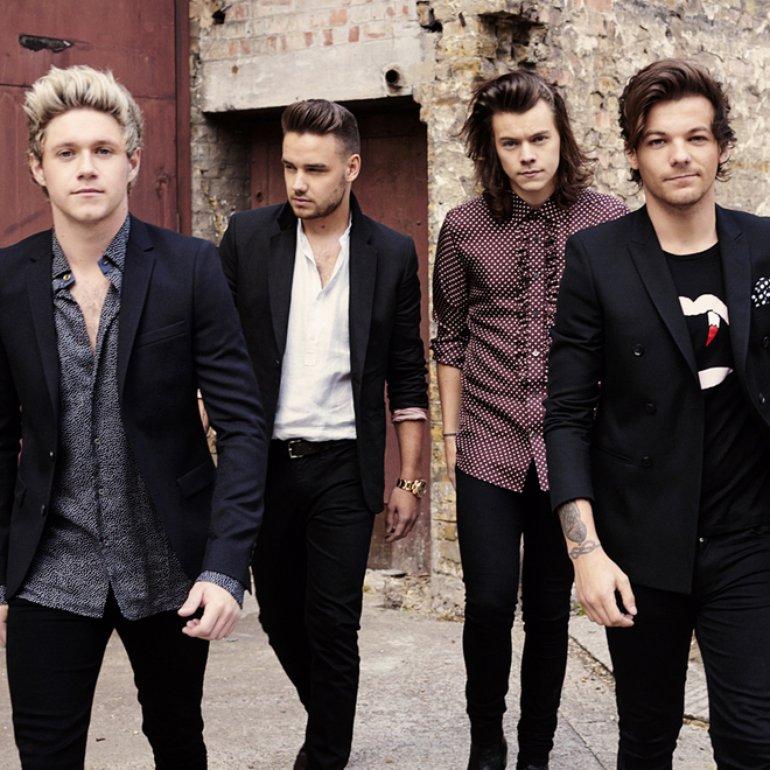 A imagem mostra os quatro integrantes da banda One Direction. Eles usam trajes social despojado. Niall, Harry e Louis olham para a câmera, Liam olha para o lado esquerdo. Eles estão de pé.