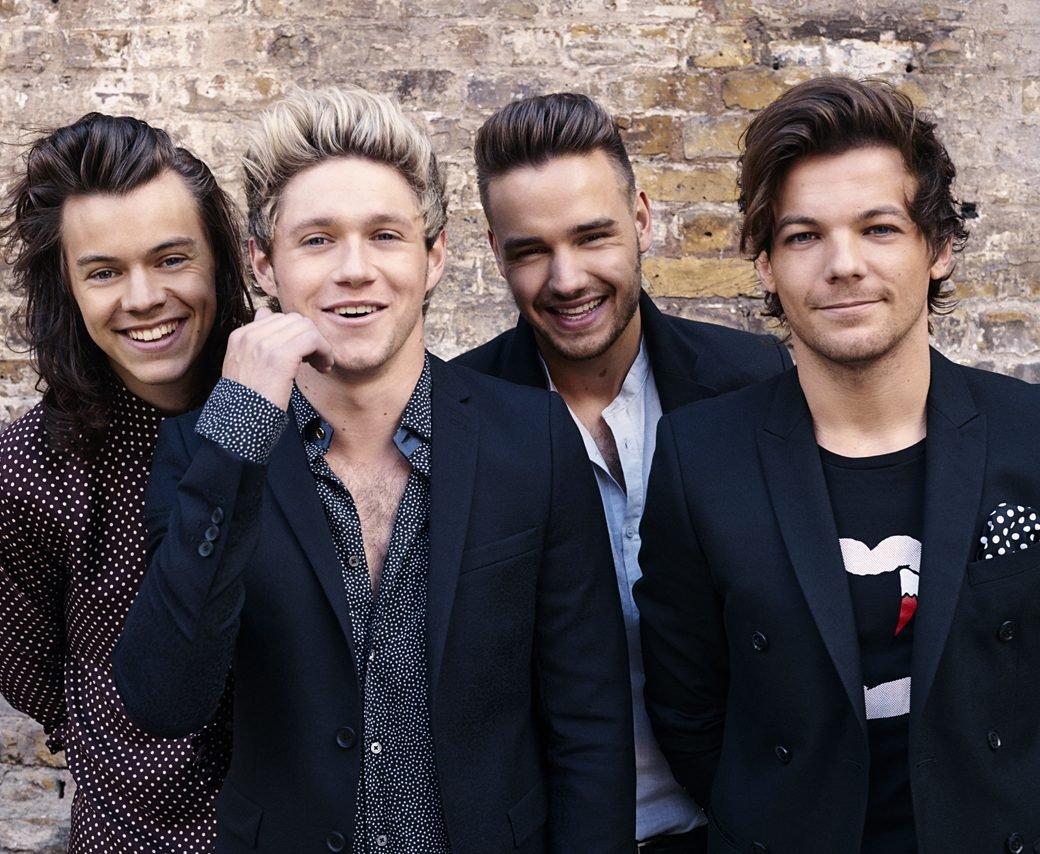 Na imagem, os quatro integrantes da banda One Direction olham para a câmera. Eles vestem traje social despojado. Harry, Niall e Liam estão sorrindo mostrando os dentes, Louis está sorrindo de boca fechada.