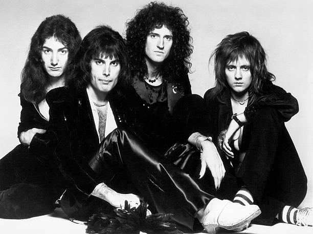 Imagem em preto e branco dos quatro integrantes da banda sentados no chão. Da esquerda para a direita estão John Deacon, Freddie Mercury, Brian May e Roger Taylor. Todos eles estão vestindo roupas pretas e possuem cabelos compridos.