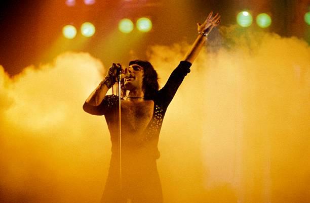 Imagem de Freddie Mercury no palco. Ele usa um macacão preto com decote em v até o meio da barriga, cabelos médios pretos e está segurando um microfone na mão direita. Sua mão esquerda está levantada para cima e ao fundo vemos uma fumaça alaranjada.