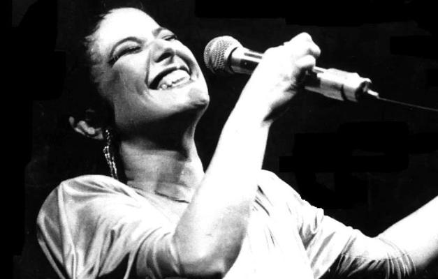A imagem em branco e preto mostra Elis Regina cantando com um largo sorriso nos lábios e os olhos fechados. Seu cabelo preto está cortado bem curto e ela segura um microfone com a mão direita, na altura da boca.