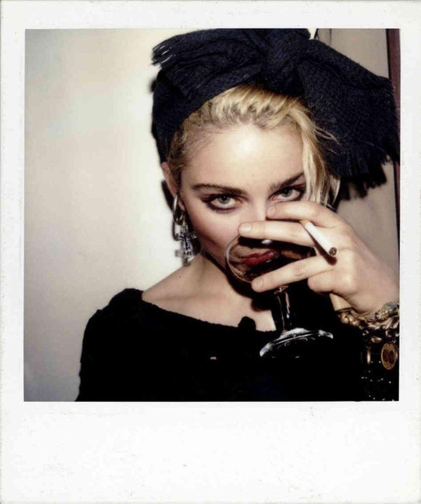 Foto em estilo Polaroid, com bordas brancas. Na parte da imagem, há a cantora Madonna quando ainda jovem adulta. Ela é uma mulher branca, de cabelos loiros, e usa um laço preto na cabeça. Ela bebe uma taça de vinho, com um cigarro entre os dedos e está olhando para a câmera.