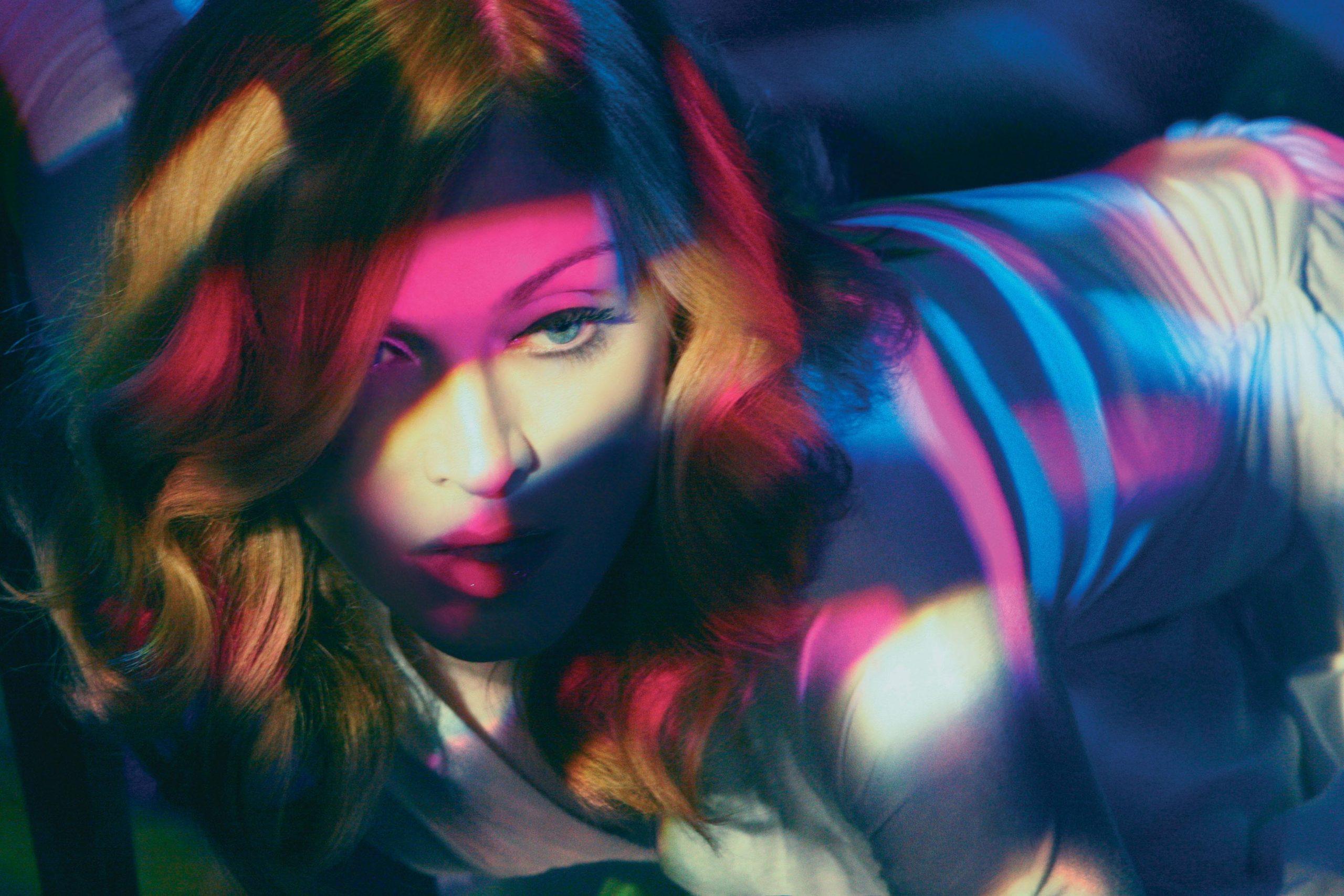 A foto mostra apenas a cabeça e o torso da cantora Madonna. Ela está apoiada de bruços, e está sendo iluminada por flashes de luz rosa, amarelo claro e azul. Ela não está olhando para a câmera.