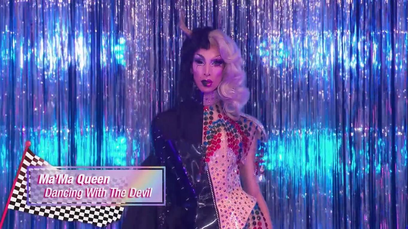 Ma'ma Queen, uma drag queen branca, veste dois vestidos em um: do lado esquerdo, ela usa tons de preto e um chifre, do lado direito prevalece a peruca loira e um maiô cheio de bolinhas e brilhos, nas cores vermelho e verde