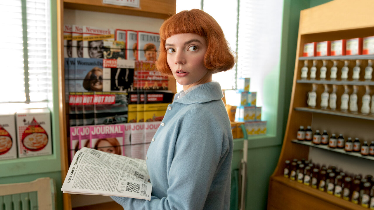 Beth Harmon, possui cabelo curto e laranja e veste um casaco azul, encara a câmera.