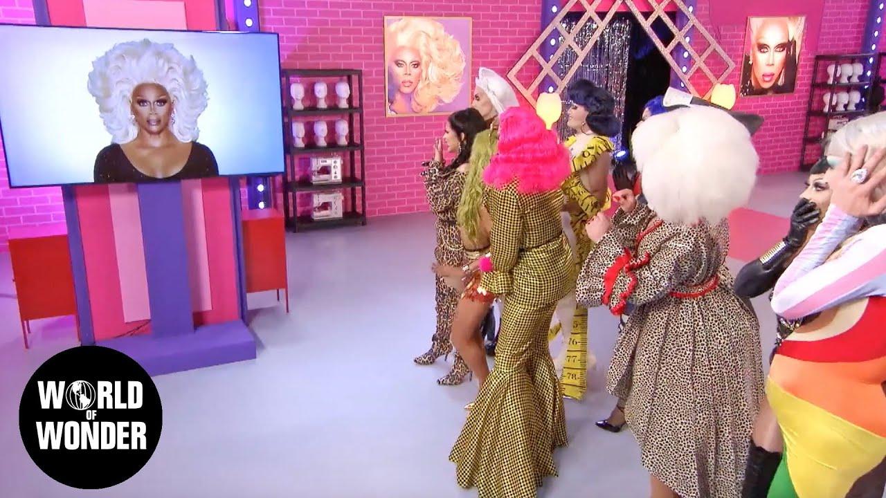 O busto de RuPaul, uma drag queen negra e de peruca branca, aparece numa TV. As drags olham para a TV.