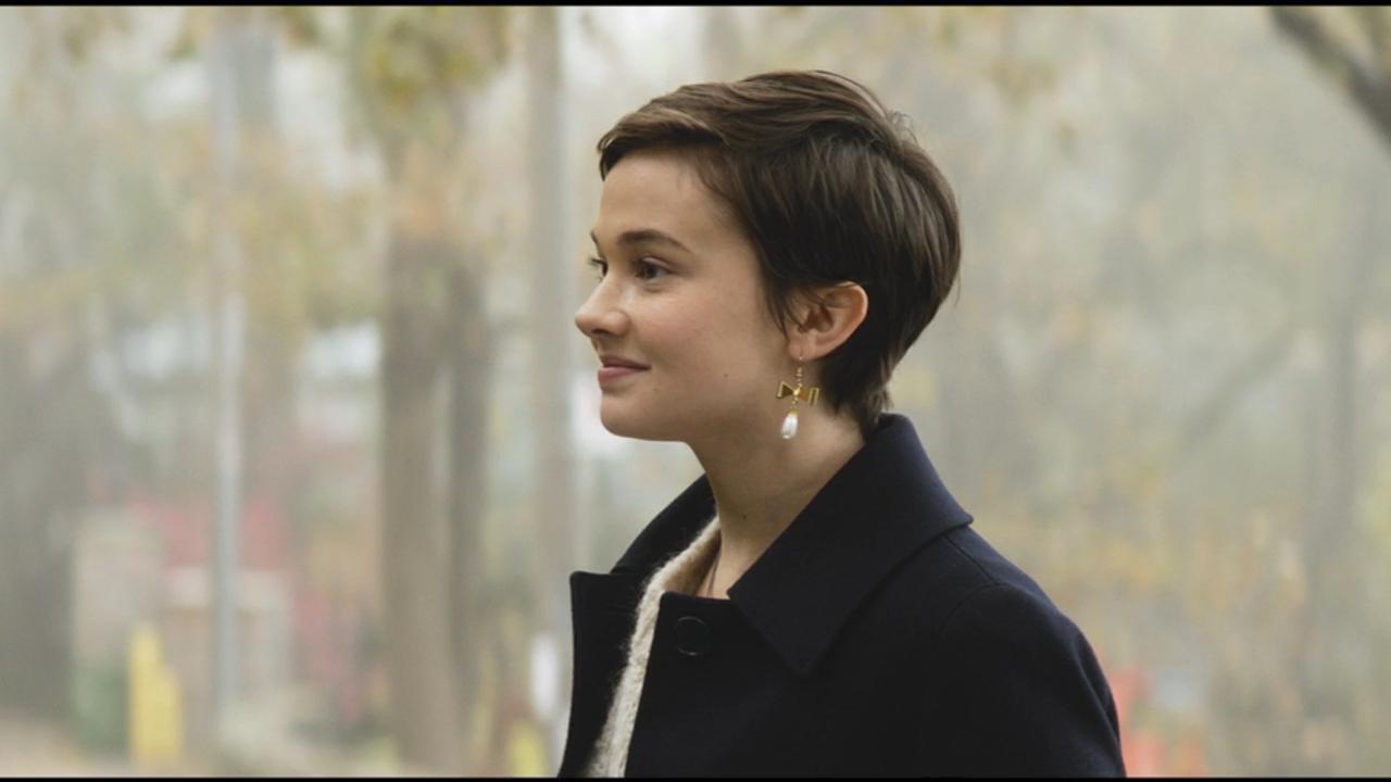 A protagonista Lily está de perfil, ela possui cabelo castanho curto e usa um casaco azul.