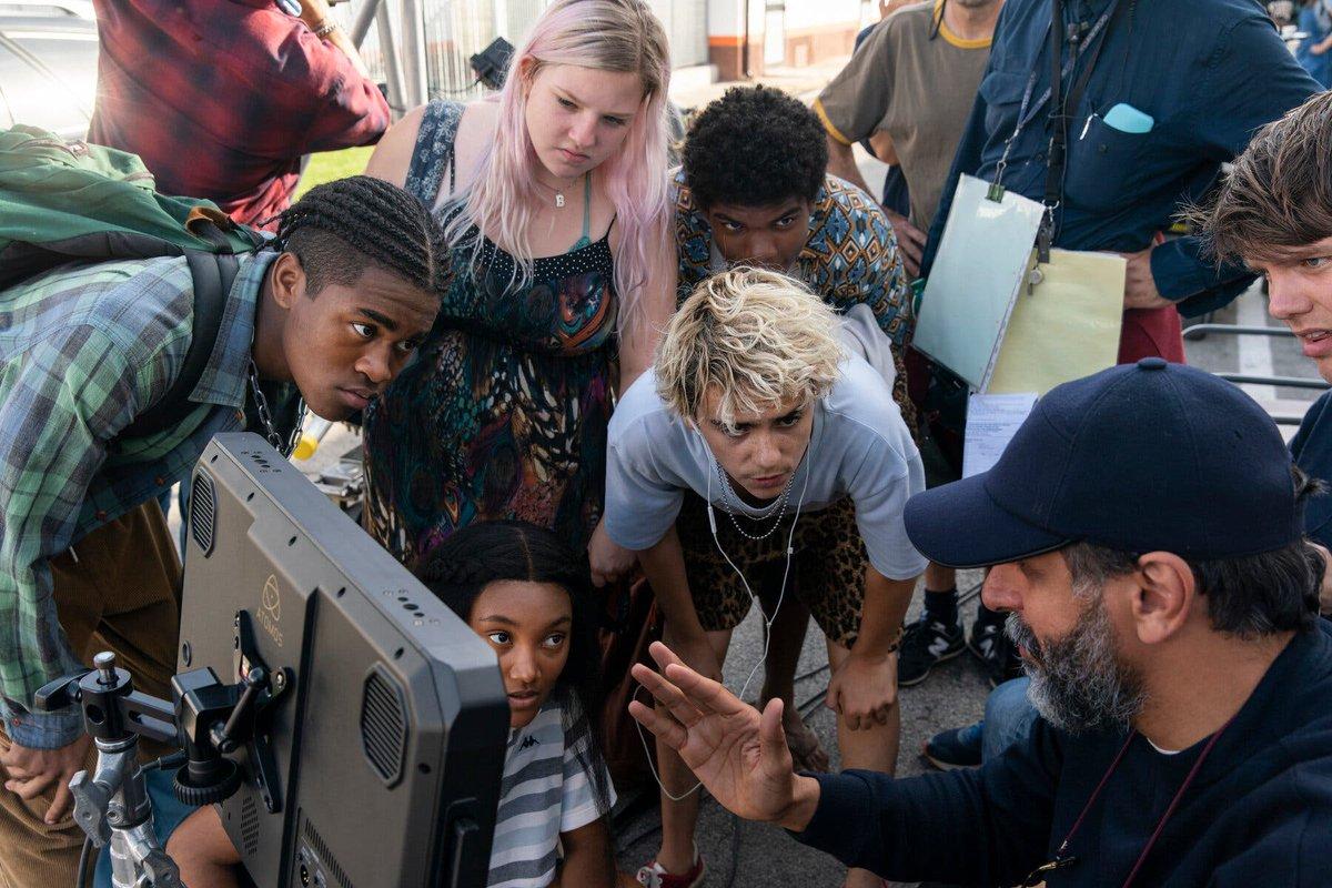Na foto, vemos vários atores ao redor de um televisor e do diretor Luca Guadagnino. Ele é o foco da imagem, ele é um homem italiano de meia idade, tem uma barba quase grisalha e usa boné e blusa azul escuro.