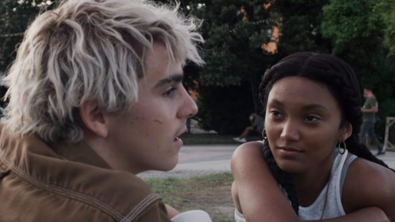 Fraser, garoto branco e de cabelo descolorido, está mais perto da câmera, de lado, enquanto Caitlin, menina negra de cabelos longos e regata branca, olha para o menino com um leve sorriso nos lábios.