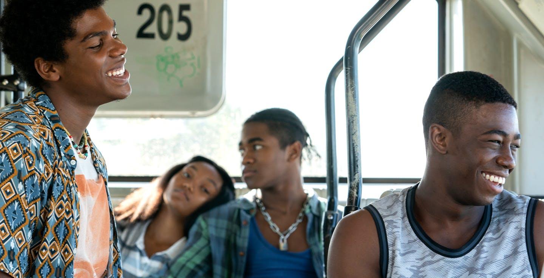 A foto é dentro de um ônibus e vemos 4 jovens negros. Na frente, Danny usa uma camisa estampada azul e laranja e sorri olhando para Craig, que usa uma regata azul. No fundo da foto e fora de foco, vemos um casal de namorados, ela deitada no ombro dele.