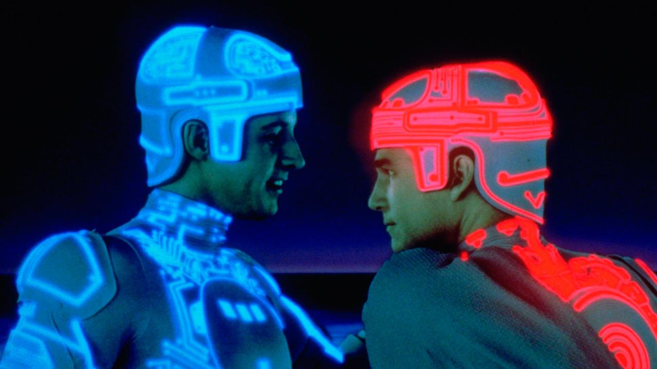 A imagem mostra dois homens brancos se encarando de perfil. O primeiro usa um capacete e uma roupa branca com fios neons azuis por toda a extensão. O segundo usa uma roupa igual, porém seus fios neons são vermelhos.