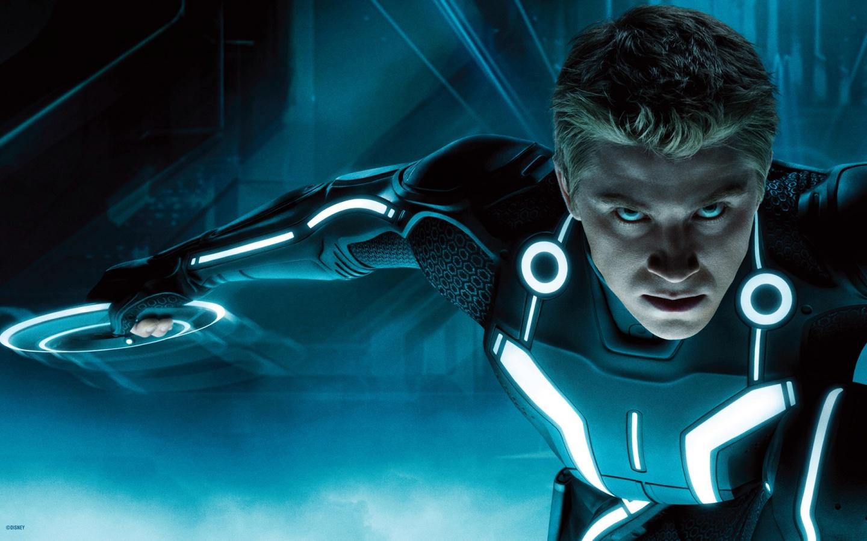 A imagem mostra o personagem de Sam Flynn. Ele é branco, tem cabelos loiros curtos, olhos azuis e usa um macacão preto com fios neons azuis pela extensão. Em sua mão direita ele segura um aro também de neon azul.