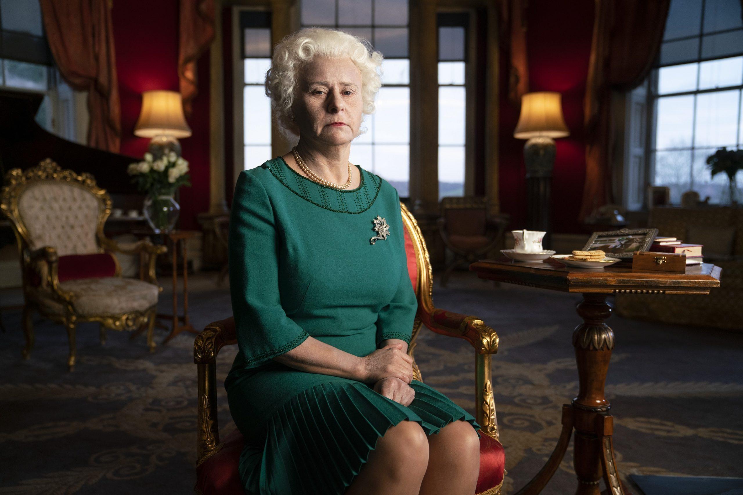 Tracey Ullman interpreta uma versão da rainha Elizabeth, uma mulher branca e idosa, de cabelos brancos e vestido verde. Ela está sentada numa cadeira dourada e vermelha e olha para a câmera com cara de nada. Ao fundo, vemos abajures, cadeiras e janelas