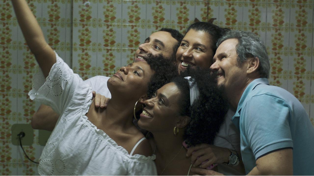 A imagem é uma das cenas do filme. Na imagem, Madá e os outros funcionários da casa estão posicionados em grupo sorrindo para uma selfie.