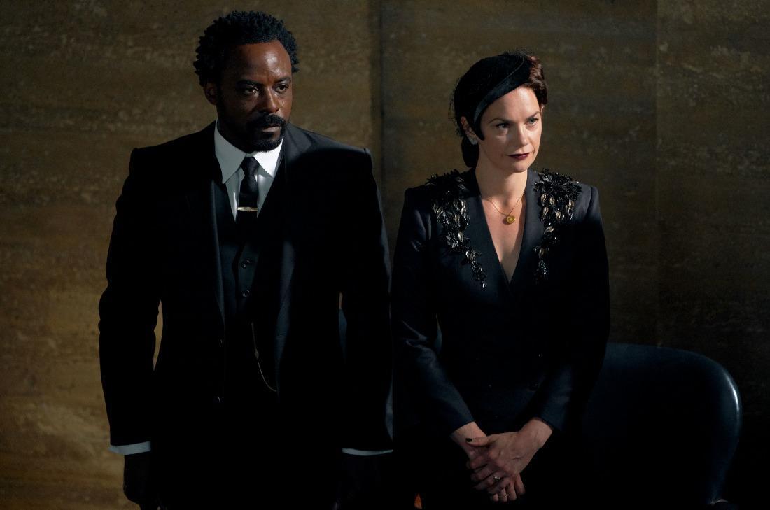 A imagem mostra Carlo Boreal, personagem de His Dark Materials, e Marisa Coulter. Carlo veste um terno preto, e Marisa um vestido preto com acessório na cabeça.