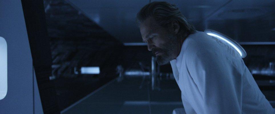A imagem mostra o personagem de Kevin Flynn de perfil em uma sala branca escura. Ele tem cabelos e barba acinzentados e usa uma blusa branca larga.