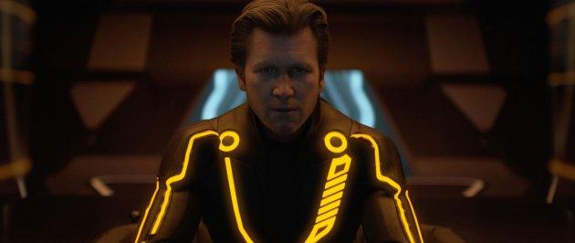 A imagem mostra o personagem Clu. Ele usa um macacão preto com fios neons laranja e tem o cabelo castanho claro e curto penteado para trás. Ele se parece com uma versão mais nova do personagem de Kevin Flynn.