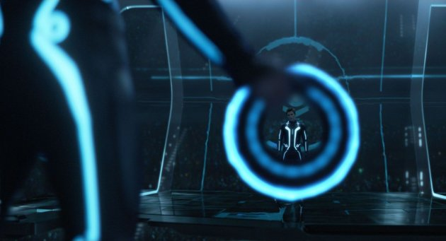 A imagem mostra uma pessoa de costas com um macacão preto com fios neons. Vemos apenas um pedaço da perna dela, que segura um aro neon nas mãos. Através do arco está a imagem de Sam Flynn, usando a mesma roupa.
